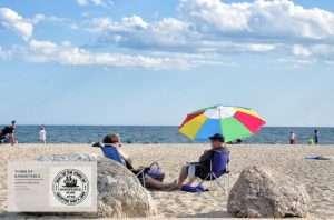 Zoom Background: couple sitting under beach umbrella enjoying the sunshine