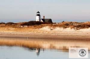 Zoom Background: Lighthouse behind dunes across the water
